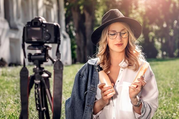 スタイリッシュな女の子ブロガーが芝生の上の通りに座っているとカメラでビデオブログを撮影します。