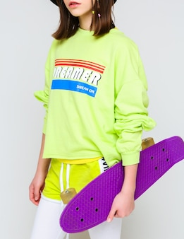 Stylish girl in a bright t-shirt, shorts and leggings holds a purple skateboard in her hands. vertical photo