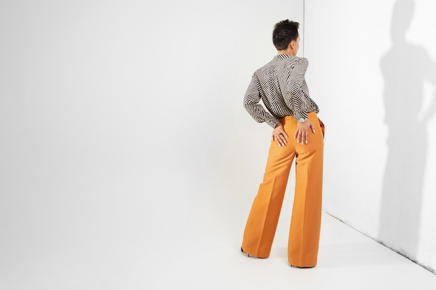Stylish girl in brown classic trousers and a shirt stands with her back against a wall on white