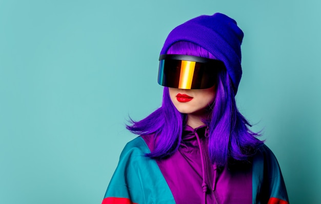 Stylish girl in cyber punk glasses and  tracksuit on blue wall