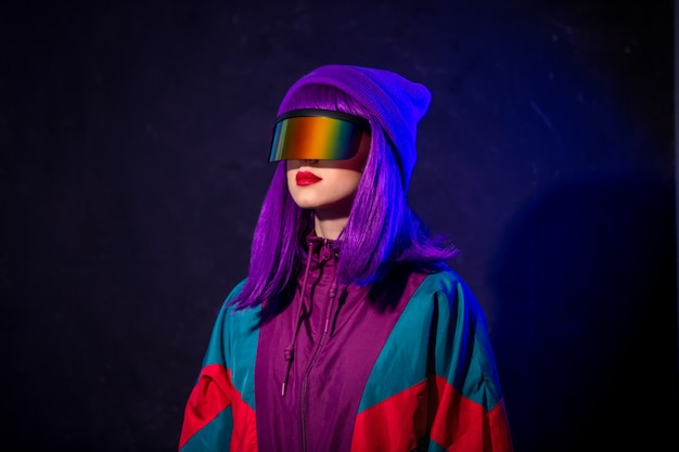Stylish girl in cyber punk glasses and  tracksuit on dark wall