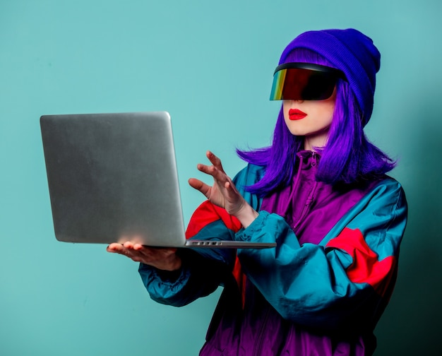 Stylish girl in cyber punk glasses and  tracksuit hold laptop computer on blue wall