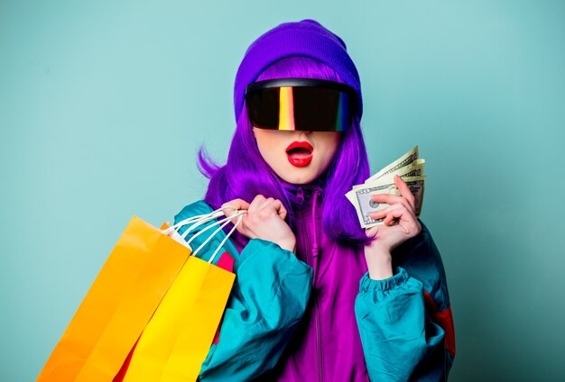 Stylish girl in cyber punk glasses and  tracksuit hold money and shopping bags on blue wall