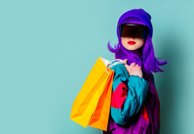 Stylish girl in cyber punk glasses and  tracksuit hold shopping bags on blue wall