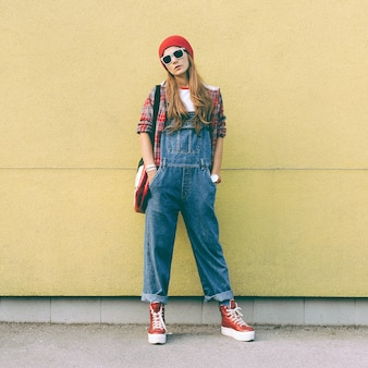 Stylish girl in denim overalls and accessories fall fashion