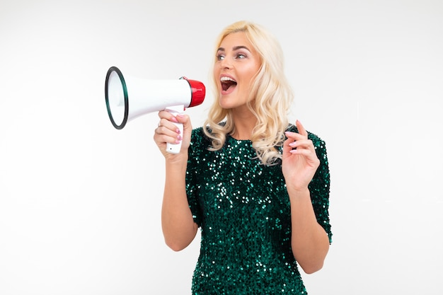 Stylish girl in a green dress speaks in a megaphone attracting attention on an isolated white background