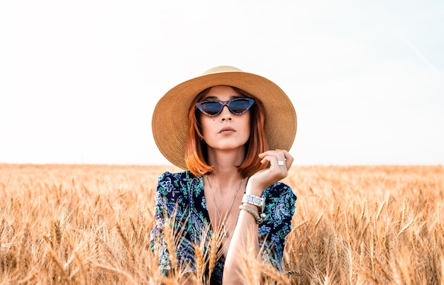 Stylish girl in a hat on a background of ears of wheat