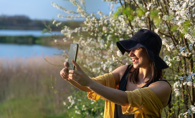 A stylish girl in a hat makes a selfie at sunset near flowering trees in the forest