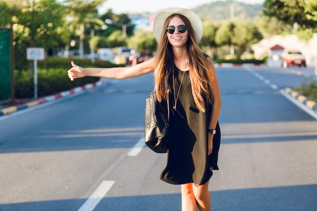 Ragazza alla moda che fa l'autostop sulla strada indossando un abito nero corto, cappello di paglia, occhiali neri e zaino nero. sorride ai caldi raggi del sole al tramonto