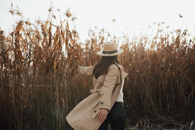 葦の背景にベージュのコートと帽子のスタイリッシュな女の子。