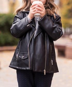 Стильная девушка в черной кожаной куртке и черных штанах позирует на городской улице со стаканом горячего напитка в руках. фото