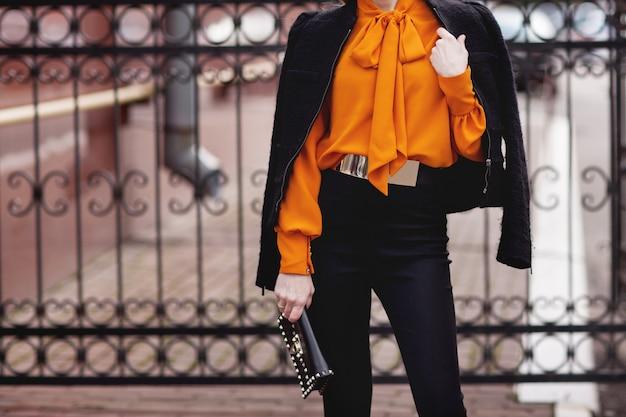 Стильная девушка в черном костюме и оранжевой блузке стоит возле забора