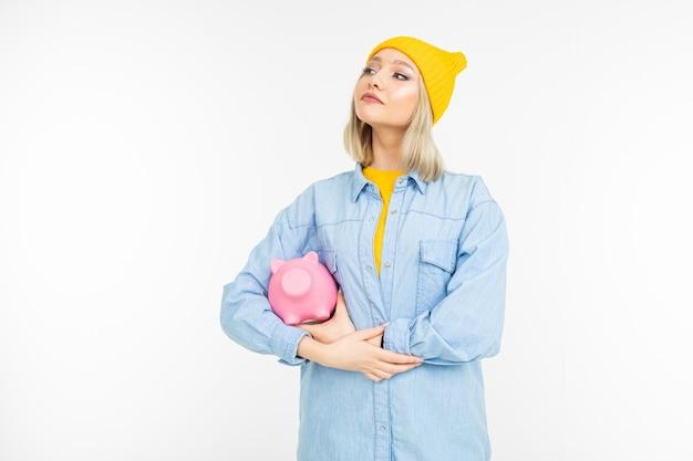 Стильная девушка в синей рубашке с банкой для экономии финансов на белом с копией пространства