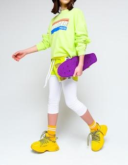 Стильная девушка в яркой футболке, шортах и леггинсах позирует с фиолетовым скейтбордом в руках. вертикальное фото