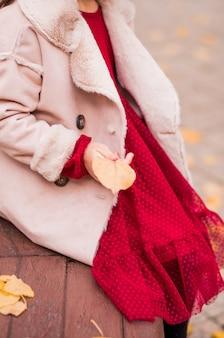 Стильная девушка в пальто, красном платье сидит на скамейке и держит в руках желтый осенний лист. фото