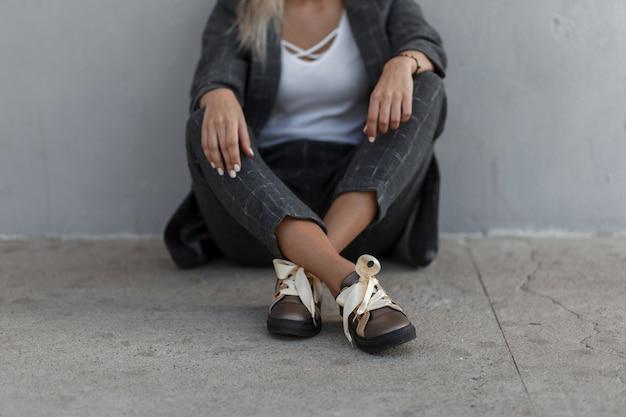 Стильная девушка в модном винтажном сером костюме с обувью сидит на улице у серой стены