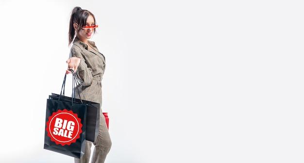 手にパッケージを持ったスーツを着たスタイリッシュな女の子。大きな売り上げ。ホリデーショッピングのコンセプト。ミクストメディア