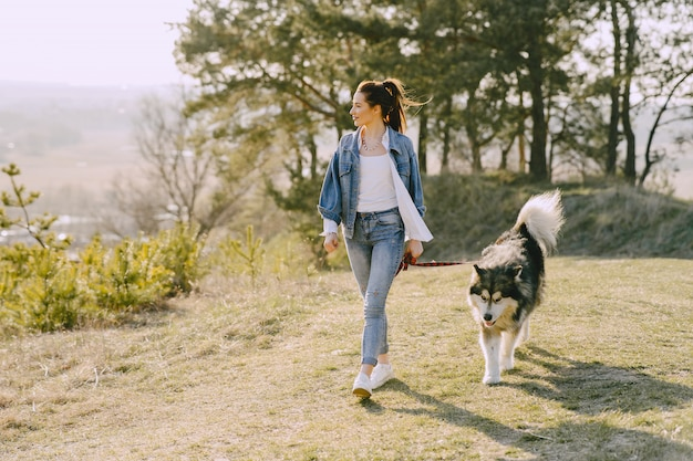 Стильная девушка в солнечном поле с собакой