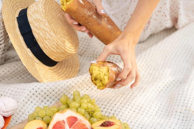 Стильная девушка в белом платье ломает хрустящий французский багет. компания веселых подруг, весело проводящих время на пикнике