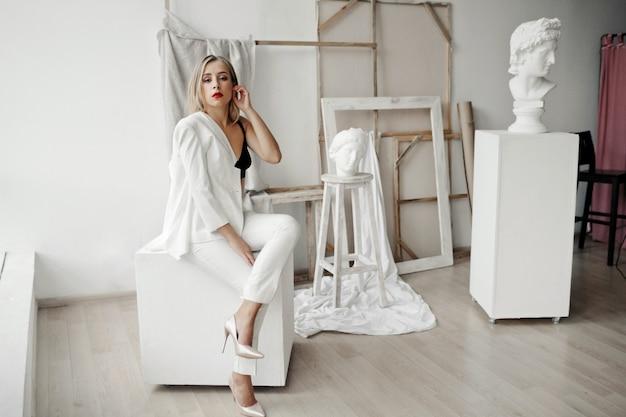 Стильная девушка в белом костюме сидит на белом кубе в галерее