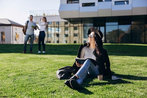 黒い帽子とコートのスタイリッシュな女の子は図書館の前に芝生の上に本とコーヒーが座っています