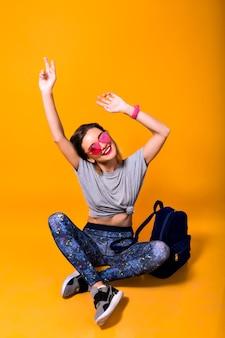 目を閉じて床に座ってバックパックと明るいメガネでスタイリッシュな女の子。スポーツシューズと黄色の背景に分離されたレギンスの若い女性のスタジオポートレート。