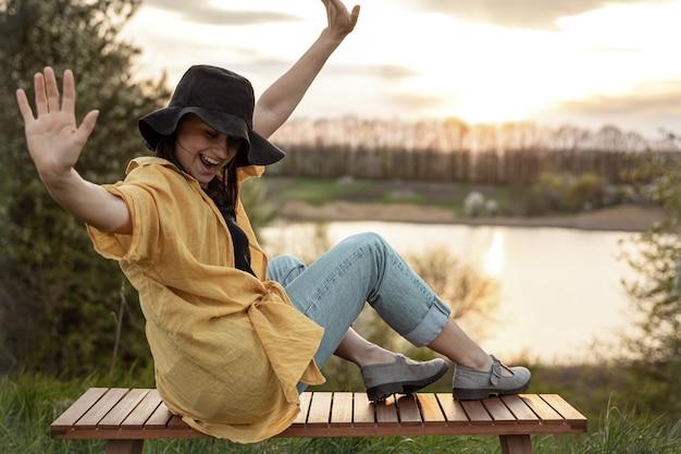 캐주얼 스타일의 세련된 소녀는 저녁에 일몰에 호수 근처에서 쉬고 있습니다.