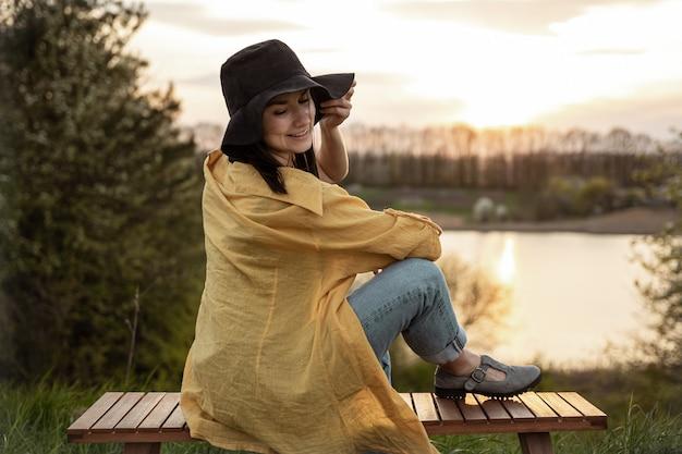 カジュアルなスタイルのスタイリッシュな女の子が夕方の日没時に湖の近くで休んでいます