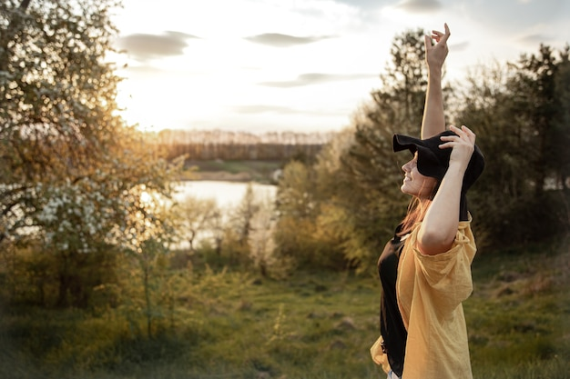 カジュアルなスタイルのスタイリッシュな女の子が笑顔で夕日を眺める