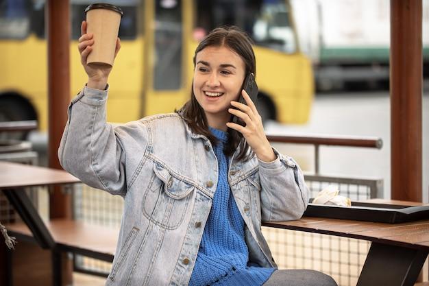 캐주얼 스타일의 세련된 소녀가 손에 커피를 들고 전화로 말하고 누군가를 기다리고 있습니다.