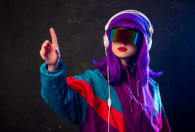 サイバーパンクメガネと暗い壁にヘッドフォンでトラックスーツのスタイリッシュな女の子
