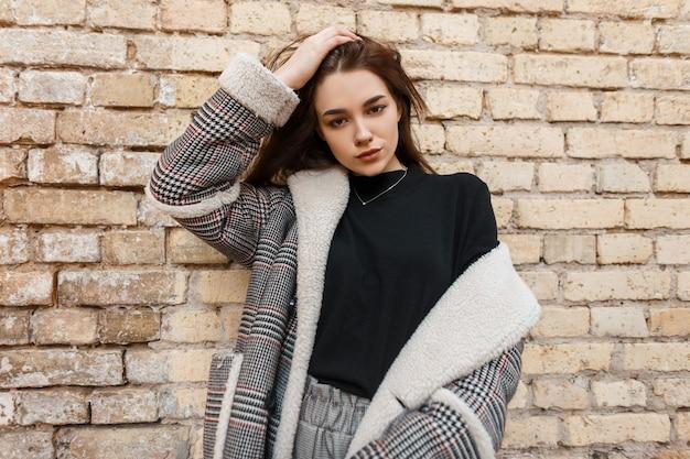 Стильная девушка в модной верхней одежде позирует на улице