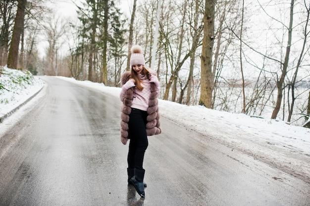 道路上の冬の日に毛皮のコートと帽子のスタイリッシュな女の子。