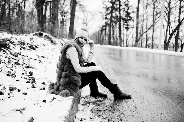 道路の境界線に座って冬の日に毛皮のコートと帽子のスタイリッシュな女の子。