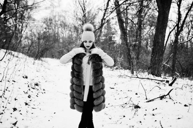 冬の森で毛皮のコートと帽子のスタイリッシュな女の子。