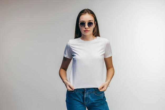 Стильная девушка в очках в белой футболке позирует в студии