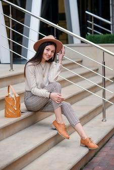 街並みの屋外でポーズをとるファッション性の高い春や秋の服を着たスタイリッシュな女の子。