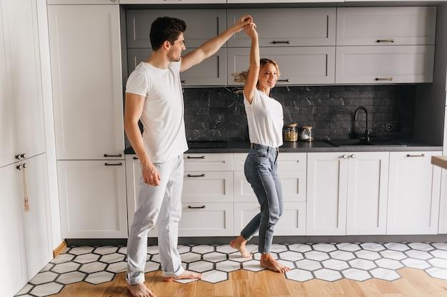 Стильная девушка в джинсах танцует с мужем утром. крытый портрет расслабленных молодых людей, весело проводящих время на кухне.