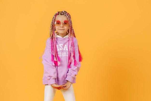 ピンクのドレッドヘアでポーズをとって丸いメガネでスタイリッシュな女の子