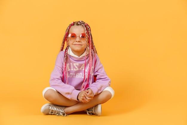 ピンクのドレッドヘアが座っている丸いメガネのスタイリッシュな女の子