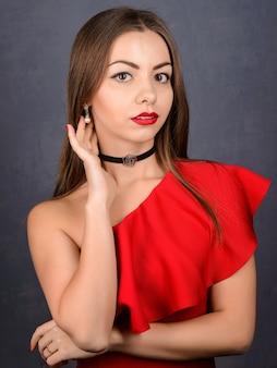 Стильная девушка в сексуальном красном платье с чувственными губами и шеей с черным колье