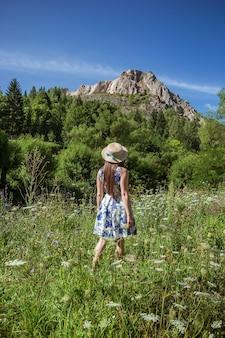 맑은 산에 여행하는 밀 짚 모자에 세련 된 소녀.
