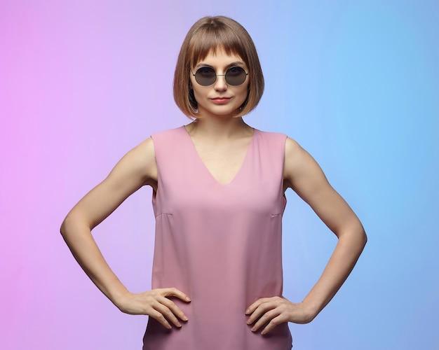 선글라스에 세련 된 소녀입니다. 분홍색 배경에 스튜디오에서 사진 촬영