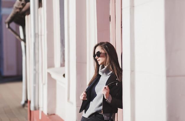 Стильная девушка в солнечных очках позирует на городской улице