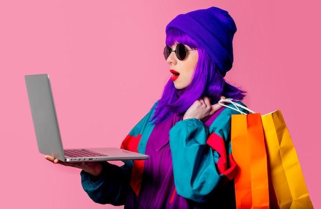 トラックスーツのスタイリッシュな女の子はピンクの壁にラップトップとショッピングバッグを保持します