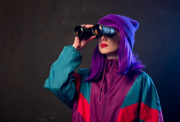 Стильная девушка в спортивном костюме с биноклем на темной стене