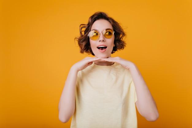 黄色の壁の近くで感情的にポーズをとる流行のtシャツのスタイリッシュな女の子