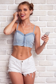 Stylish girl is listening to music using a smart phone.