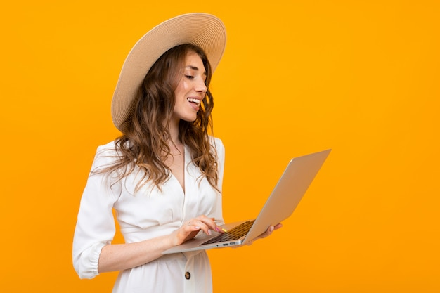 Stylish girl is typing on a laptop against a yellow wall