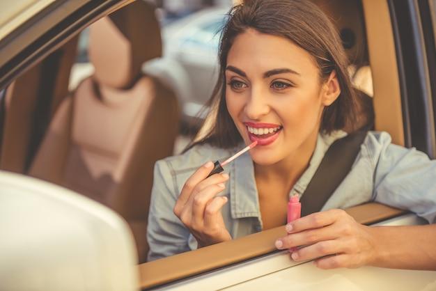 Стильная девушка использует блеск для губ и улыбается во время вождения.